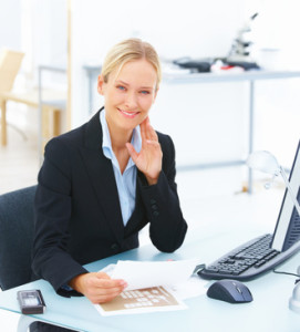 Portrait of a young smiling business woman sitting at office